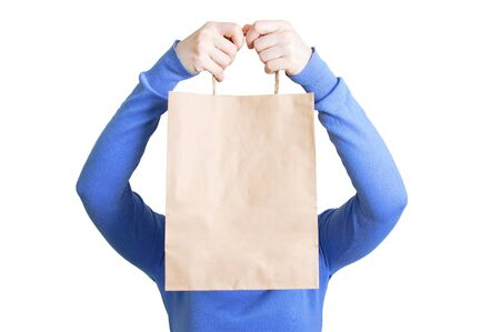Caucasian girl with a craft package in her hands covers her face. White isolate.