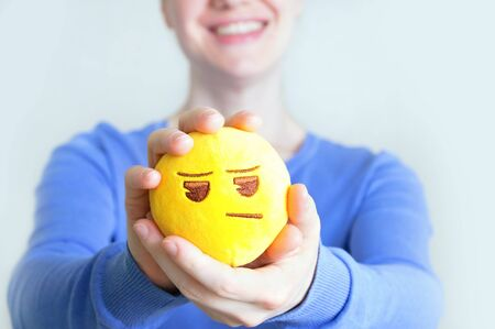 Yellow round soft toy sad emoticon in the hand of a caucasian girl. Young woman smiling. Reklamní fotografie