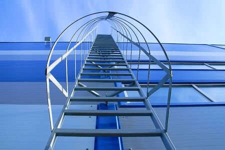 A metal staircase on the facade of an industrial blue building. View from below. Reklamní fotografie