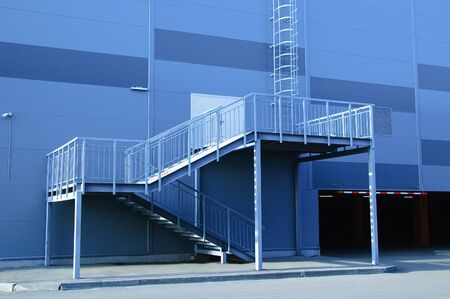 A metal staircase on the facade of an industrial blue building. Reklamní fotografie