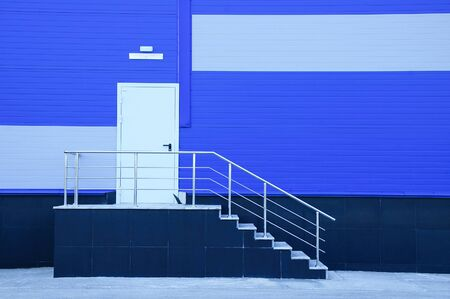 Service entrance and metal staircase on the facade of an industrial blue building.
