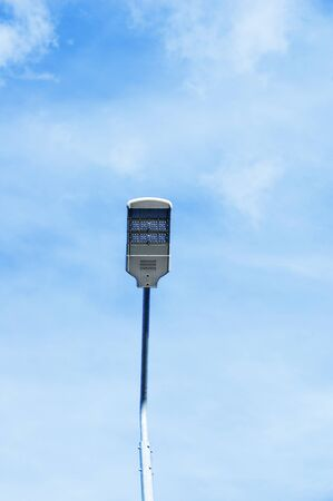 Electric street lamp against the blue sky with clouds in the afternoon.