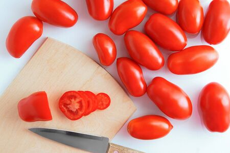 Red plum variety tomatoes on a wooden cutting board with a knife on a white background. View from above.
