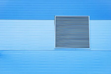 Close-up metal ventilation grill on the facade of a blue building.