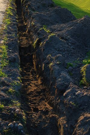 Dug in the ground trench for the pipeline. In the evening on the city street. Reklamní fotografie