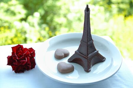 Chocolate dessert on a plate the Eiffel Tower and two hearts and a red flower. Outdoors. Reklamní fotografie