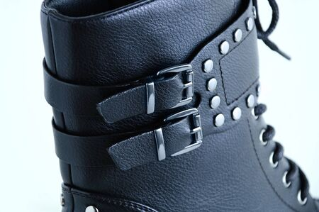 Clasps on black boots close-up with metal rivets. White background.