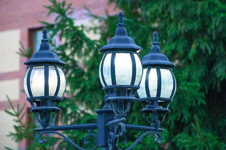 Street vintage lantern close-up on the background of the house and vegetation.