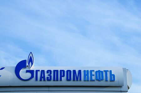 Russia 09-25-2019. Gas station sign on a background of blue sky. Russian text Gazpromneft.