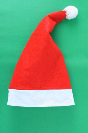Christmas red Santa hat on a green background. Vertical photo