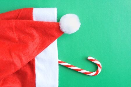 Christmas red santa hat and caramel on a green background.
