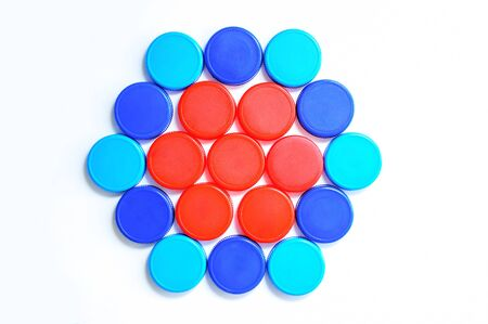 Plastic multi-colored caps laid out in the shape of a figure for bottles on a white background. Close-up.