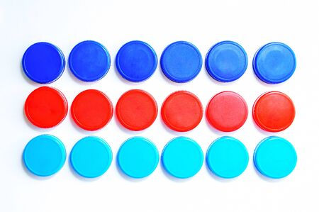 Plastic multi-colored bottle caps are arranged in three rows on a white background. Close-up.