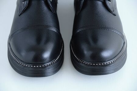 The toe of black boots close-up. White background.