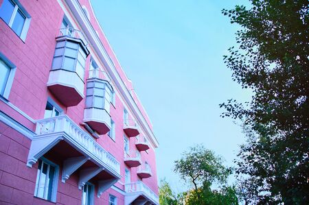 Facade of a pink house with balconies and foliage of trees. View from below.