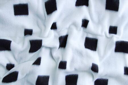 Woolen white plaid close-up with a square black print. Reklamní fotografie