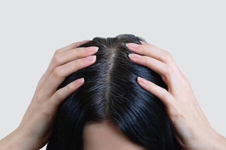 Hoofd van een blanke vrouw met zwart grijs haar. Vingers in het haar. Stockfoto