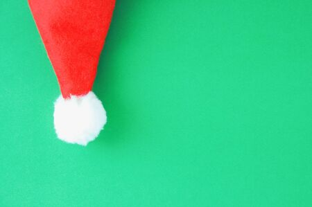 Christmas red Santa hat close-up on a green background.