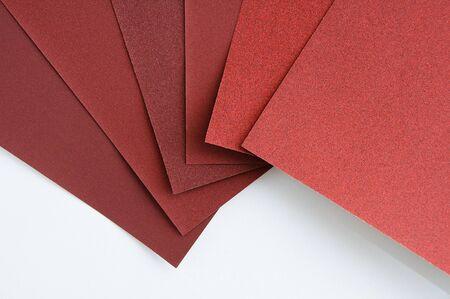 Sheets of brown sanding paper on a white background. Close-up.