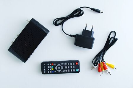 Black set-top box for digital television, control panel, euro plug for network connection on a white background.