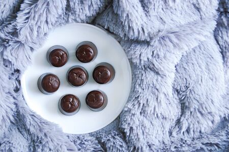 Chocolate candies on a white plate on a gray fur plaid.