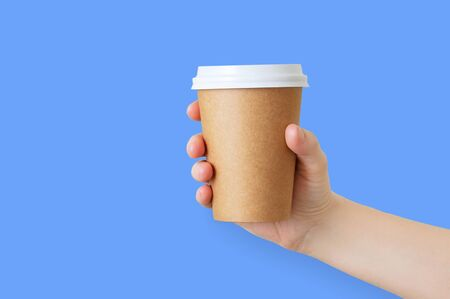 Paper brown cup of coffee in the hand of a caucasian girl. Blue background.