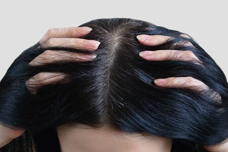 Head of a caucasian woman with black gray hair. Fingers in hair.