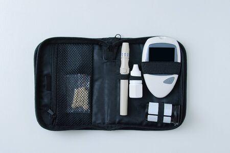 Set for measuring blood sugar in a black case. Electronic glucometer, lancet and test strip on a white background. Reklamní fotografie
