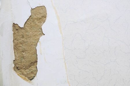 Damaged wall in the room. The fallen off plaster close-up. Archivio Fotografico