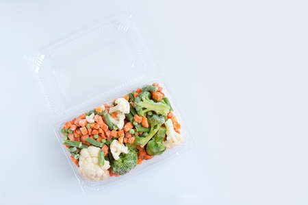 Frozen vegetable mix in a transparent plastic container on a white background.