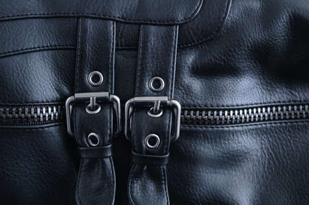 Two metal buckles on a black leather shoe close-up.