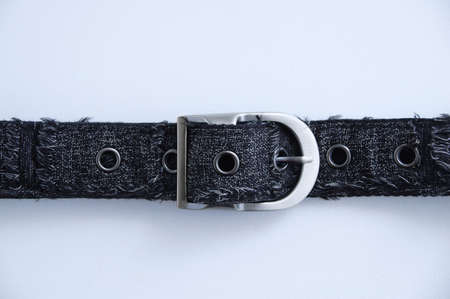 Fastened metal buckle of a man gray textile belt on a white background close-up.