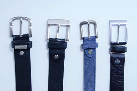 Four metal buckles male black leather and blue on a white background close-up.