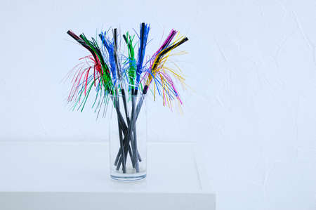 Black straws in a glass with a Christmas shiny fringe. White background.