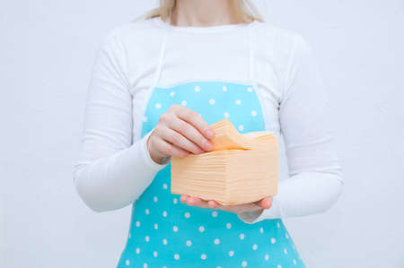 Caucasian woman housewife in a blue apron with yellow paper napkins in her hands. Banque d'images