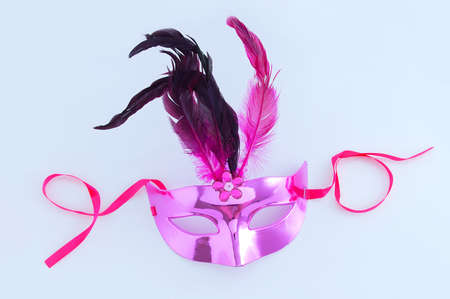 Purple masquerade face mask with feathers. White background.