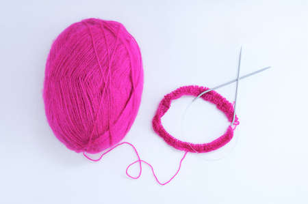 Knitting needles and a skein of purple wool. White background.
