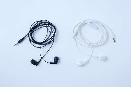 The wired small headphones are black and white. White background. Banque d'images