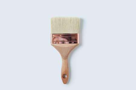 Paint brush with a wooden handle close-up on a white background.
