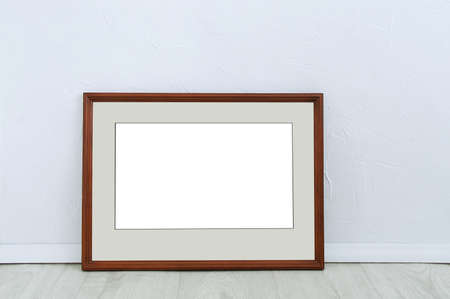 Wooden brown frame with mat on the floor of the room against the white wall.