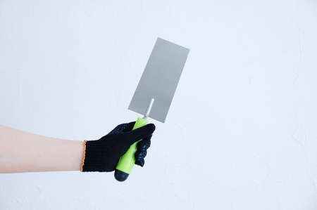 A metal trowel for cement in the hand of a Caucasian girl. White background.