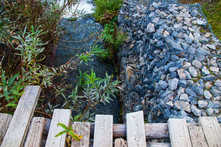 Strengthening the gully zone by the stream with stones and wooden bridge flooring of planks in the summer outside in the afternoon. Banque d'images - 158410797
