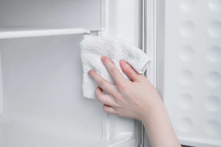 Caucasian woman wipes the freezer of the refrigerator with a rag close-up. Banque d'images - 158953008