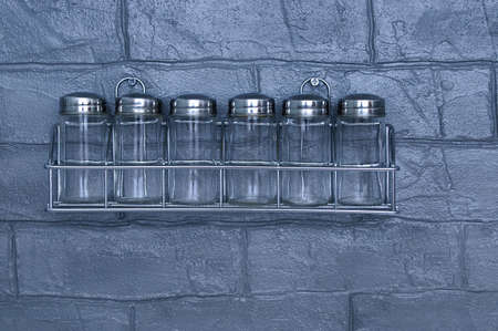 Empty glass spice jars on a gray brick kitchen wall. Banque d'images
