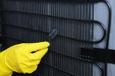 A hand in a yellow glove cleans the fridge radiator grill with a toothbrush close-up.