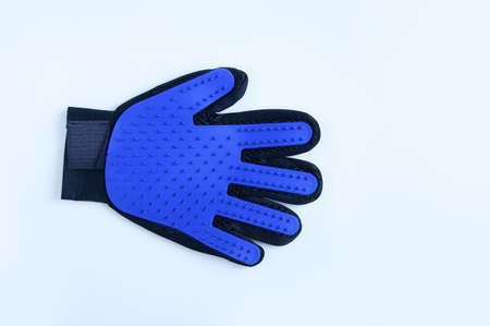 Blue rubber mitten glove for combing pet hair. White background.