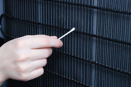 Hand cleans the radiator grill of the refrigerator with a cotton swab close-up.