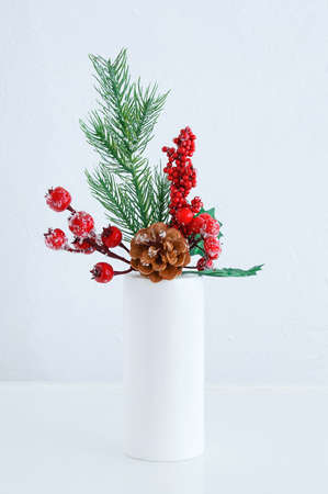 Christmas branch of a tree with ice, red berries and a pine cone in a white vase. White background. Banque d'images - 159211970