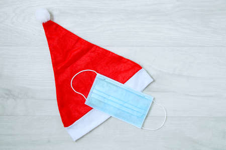 Red Christmas santa hat and medical protective mask. Gray wooden background.