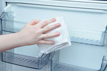 Caucasian woman hand with a cotton rag washes the refrigerator door. Banque d'images - 159428775